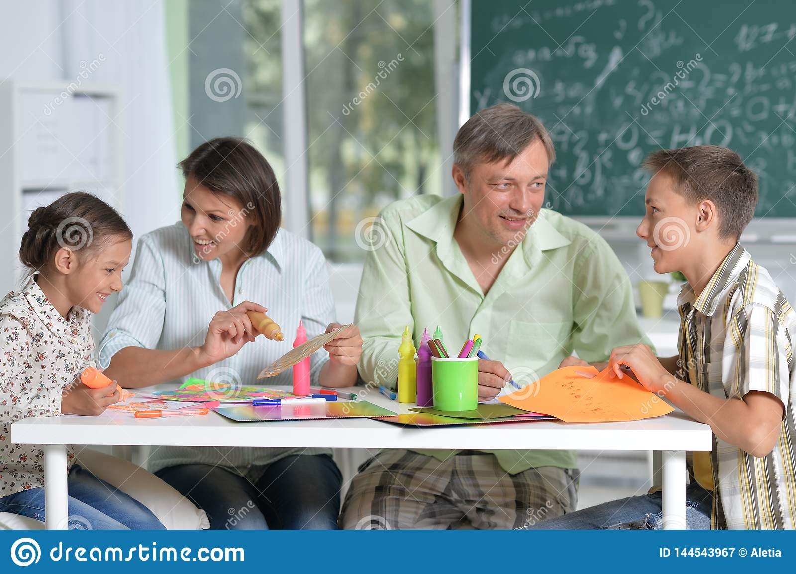 Portrait of happy family of four drawing together at home