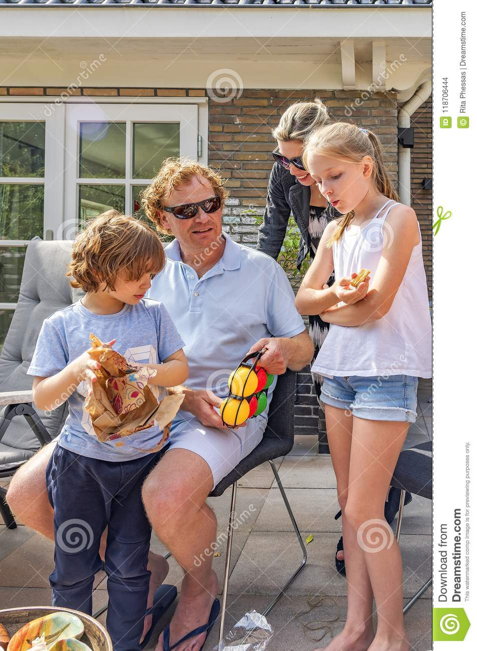 Portrait of a happy family in the garden. A little boy picks up his birthday present, his father, mother, and sister admire the gi