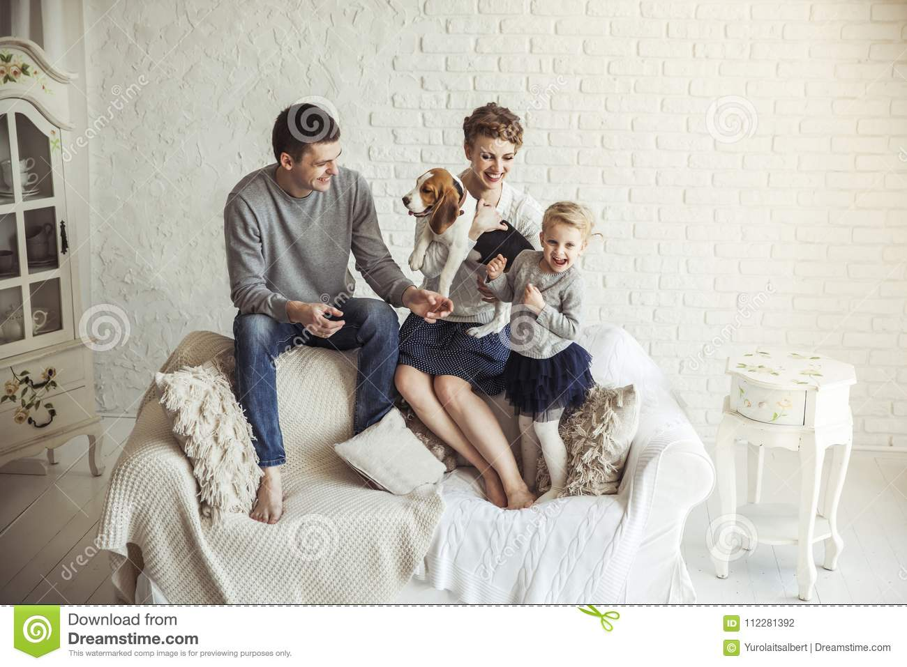 Portrait Of Happy Family With Pet Dog On Sofa In Living Room Stock ...