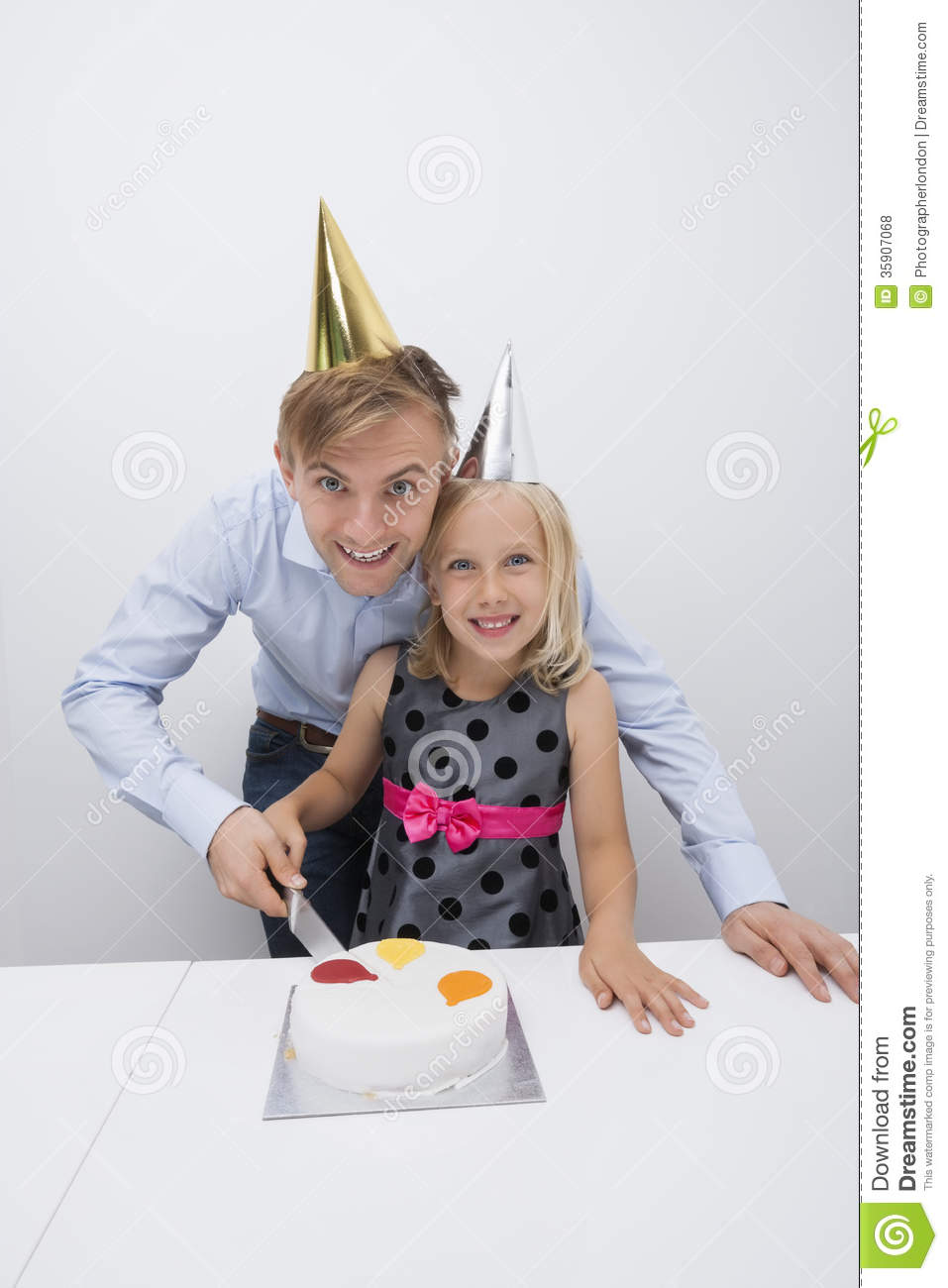 Portrait Of Happy Father And Daughter Cutting Birthday Cake At Table