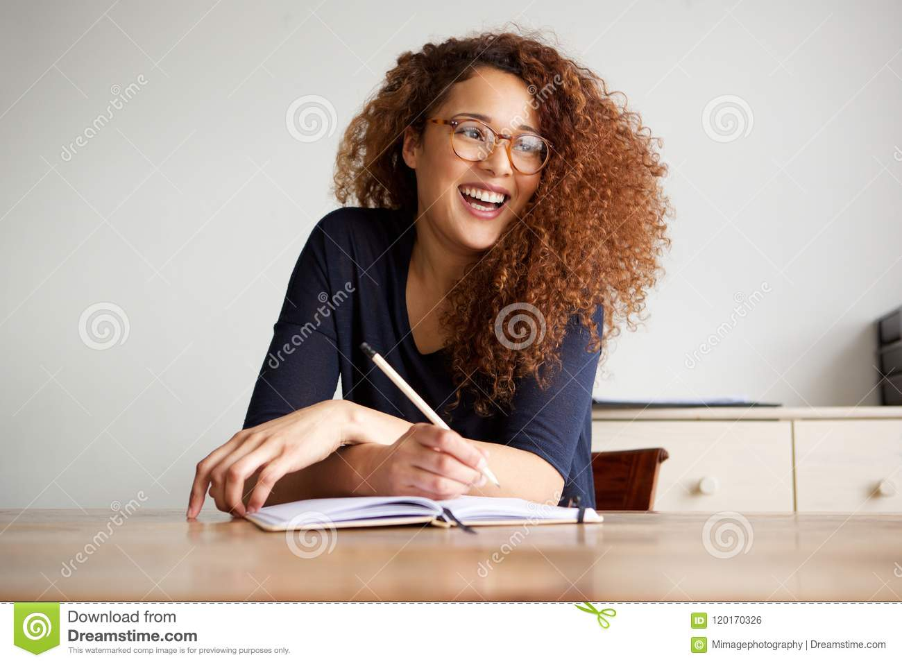 Happy female college student sitting at desk writing in book