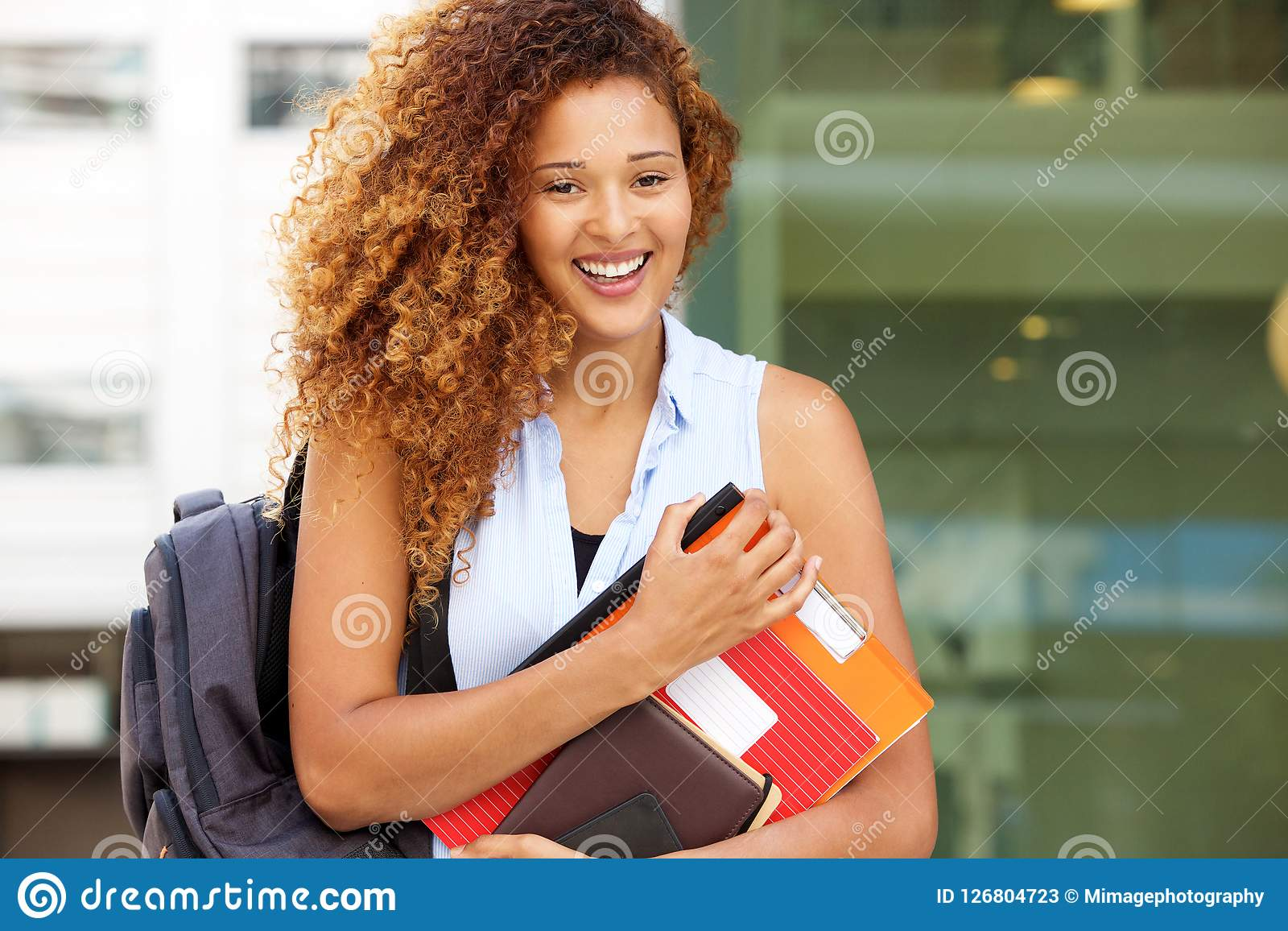 Happy female student smiling with bag and books on campus