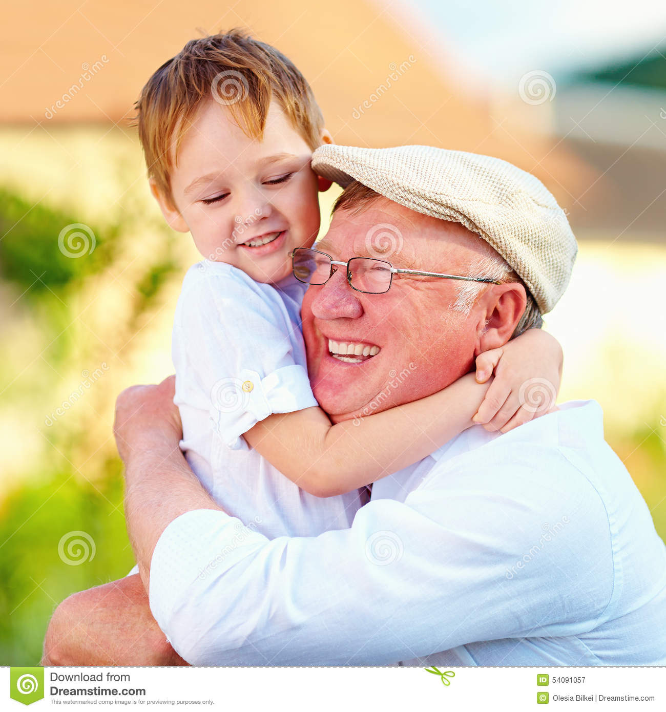 portrait of happy grandpa and grandson embracing outdoors stock