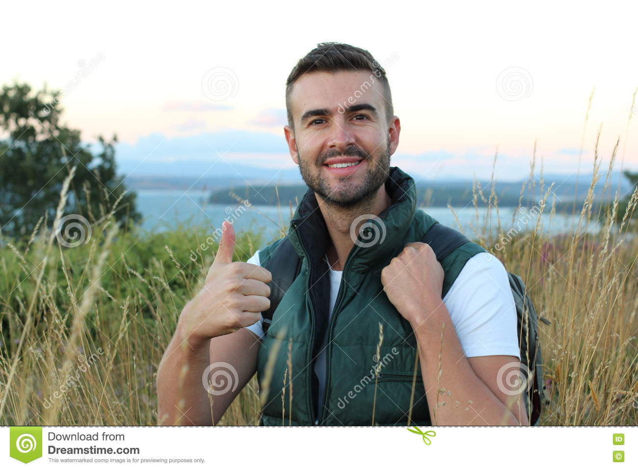 Portrait of a happy handsome man with backpack hiking into the forest with stunning view from a top of a mountain