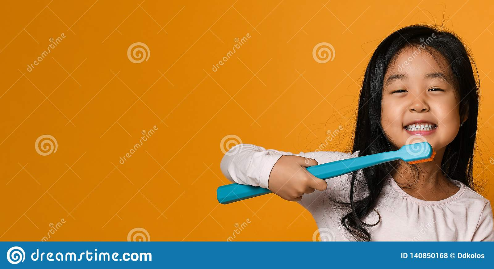 Portrait of a little girl holding a tooth brush over yellow background