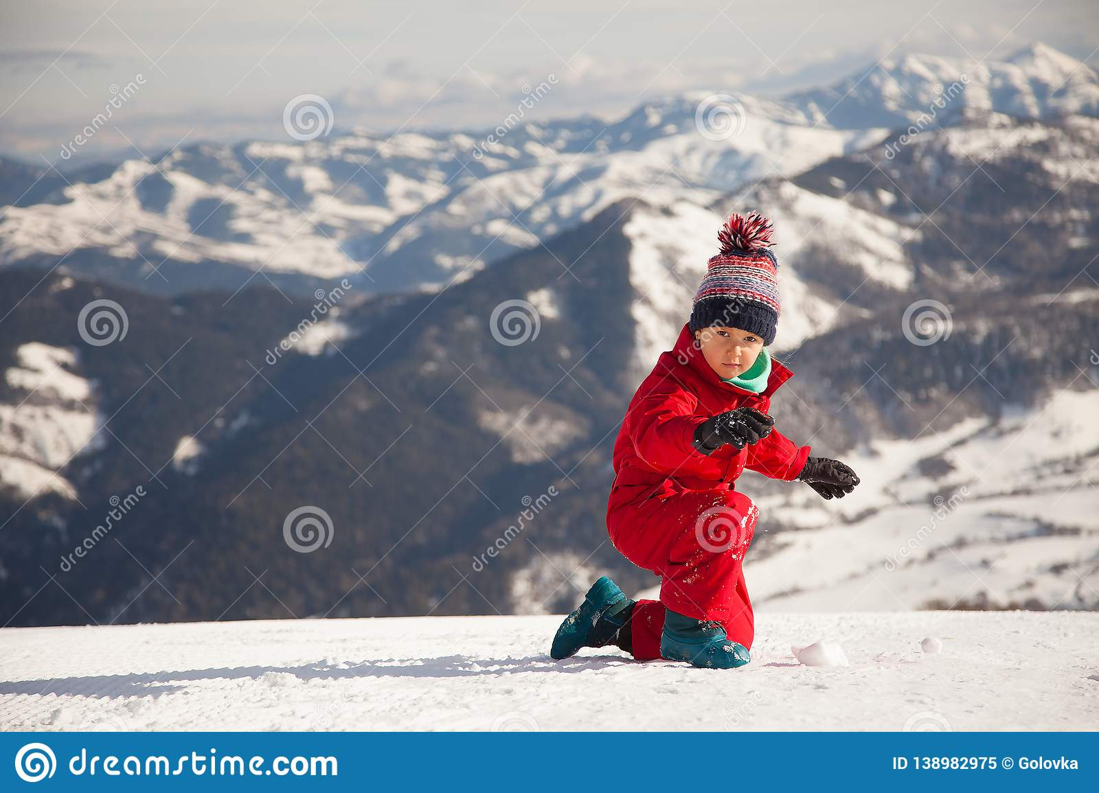 Portrait of happy little girl playing on the top of mount with ice and snow