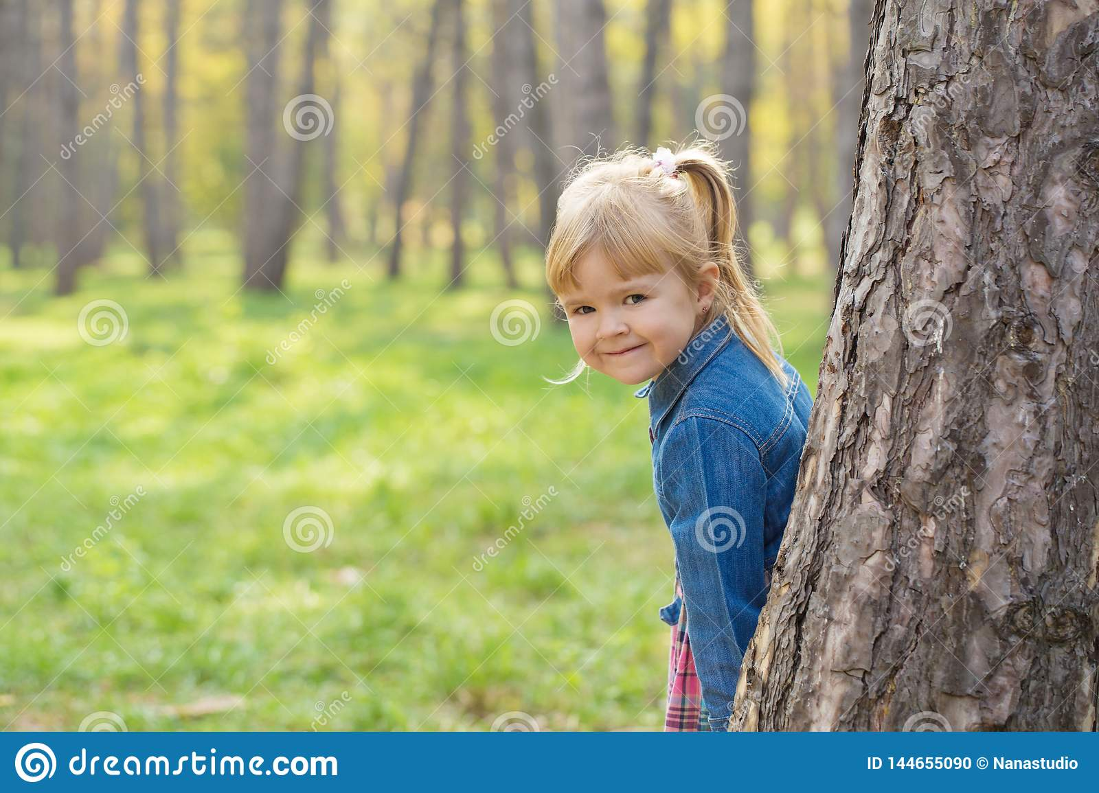 Portrait of a happy little girl with a smile on her face hiding behind a tree