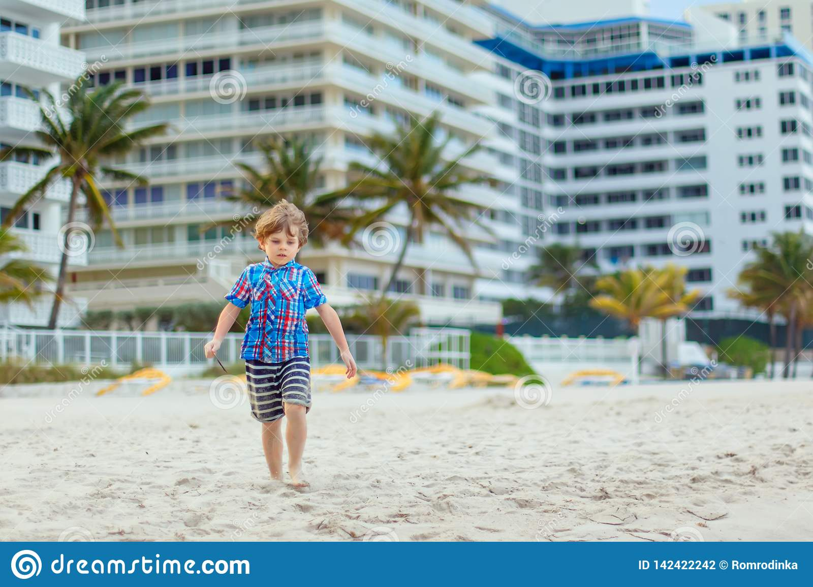 Portrait of happy little kid boy on the beach of ocean. Funny cute child making vacations and enjoying summer. Healthy