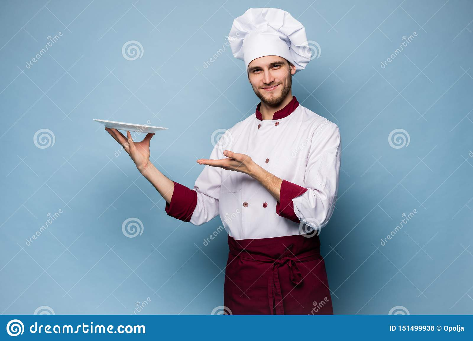 Portrait of a happy male chef cook standing with plate isolated on light blue background.