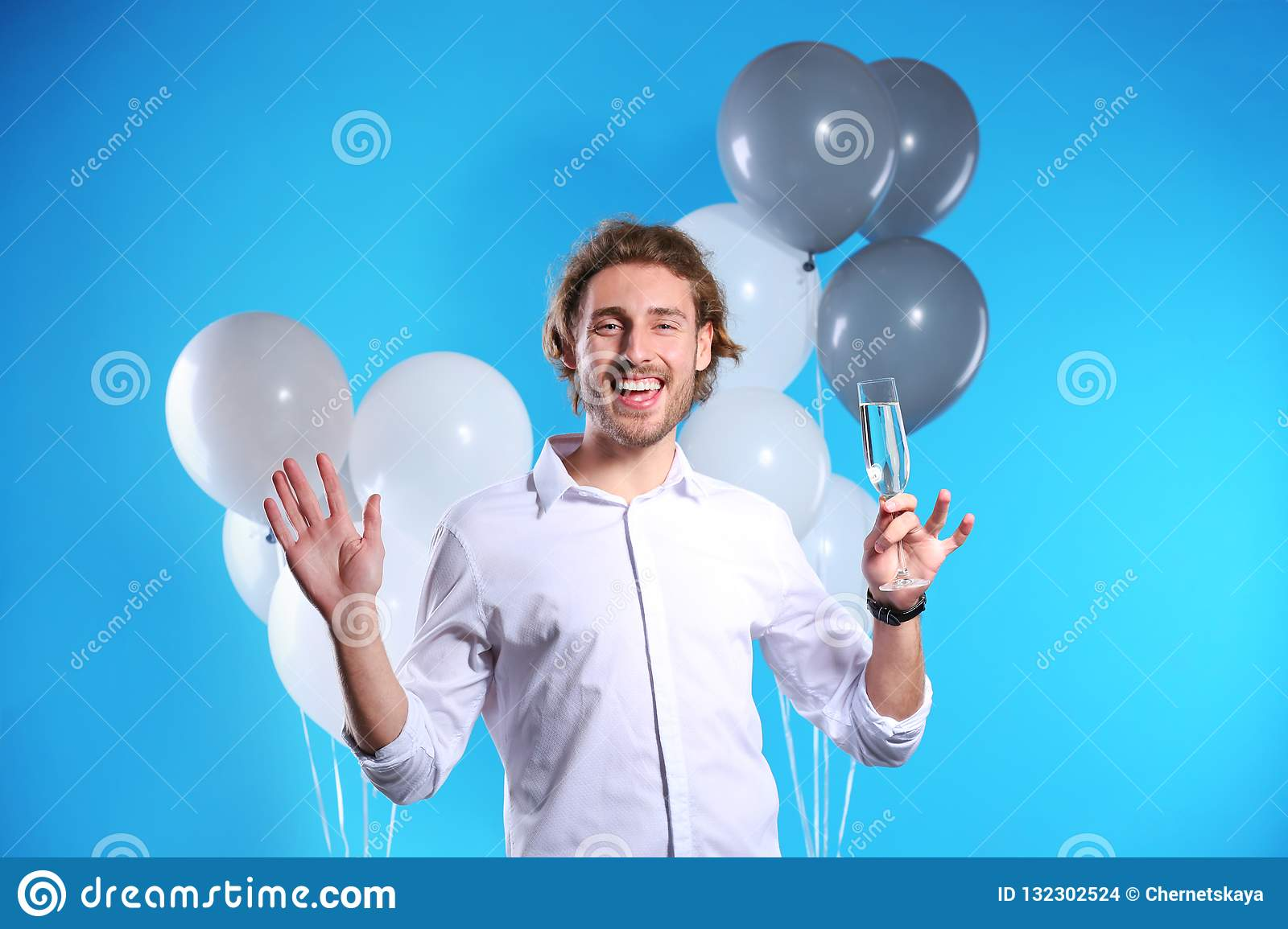 Portrait of happy man with champagne in glass and party balloons