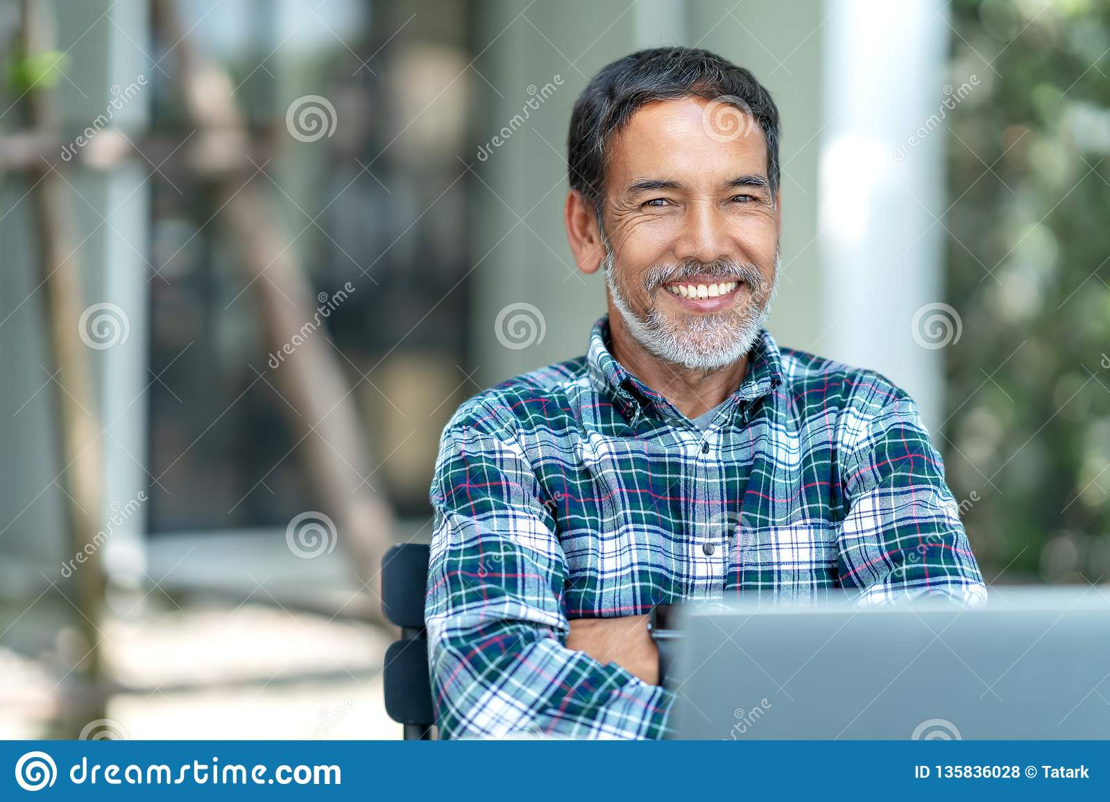Portrait of happy mature man with white, grey stylish short beard looking at camera outdoor. Casual lifestyle of retired hispanic