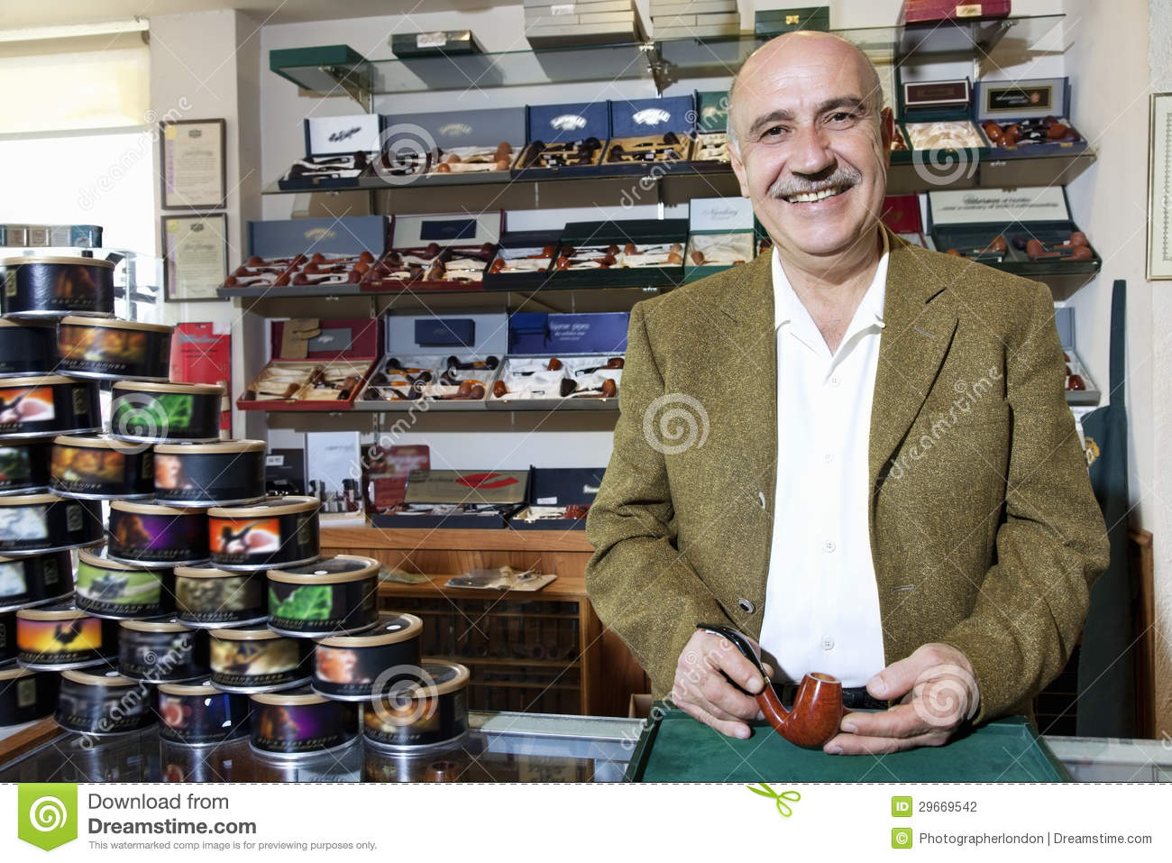 Portrait Of A Happy Mature Tobacco Shop Owner With Cans On