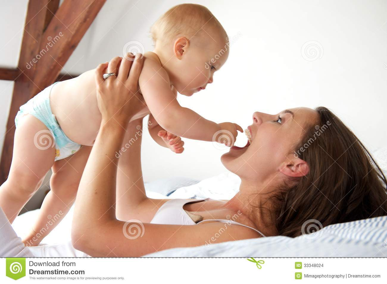 Baby bed next to mom - Portrait Of A Happy Mother And Baby Playing In Bed Stock Images