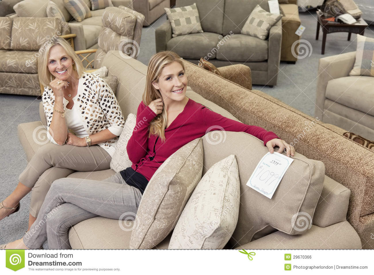 Portrait Of Happy Mother And Daughter Sitting On Sofa In Furniture