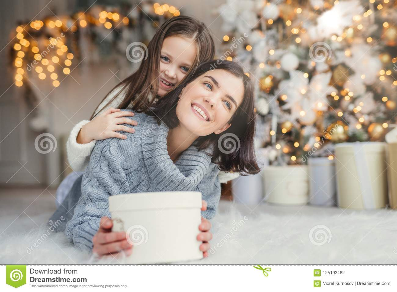 Portrait of happy mother and daughter spend free time together, embrace each other, have pleasant smiles, hold wrapped present box