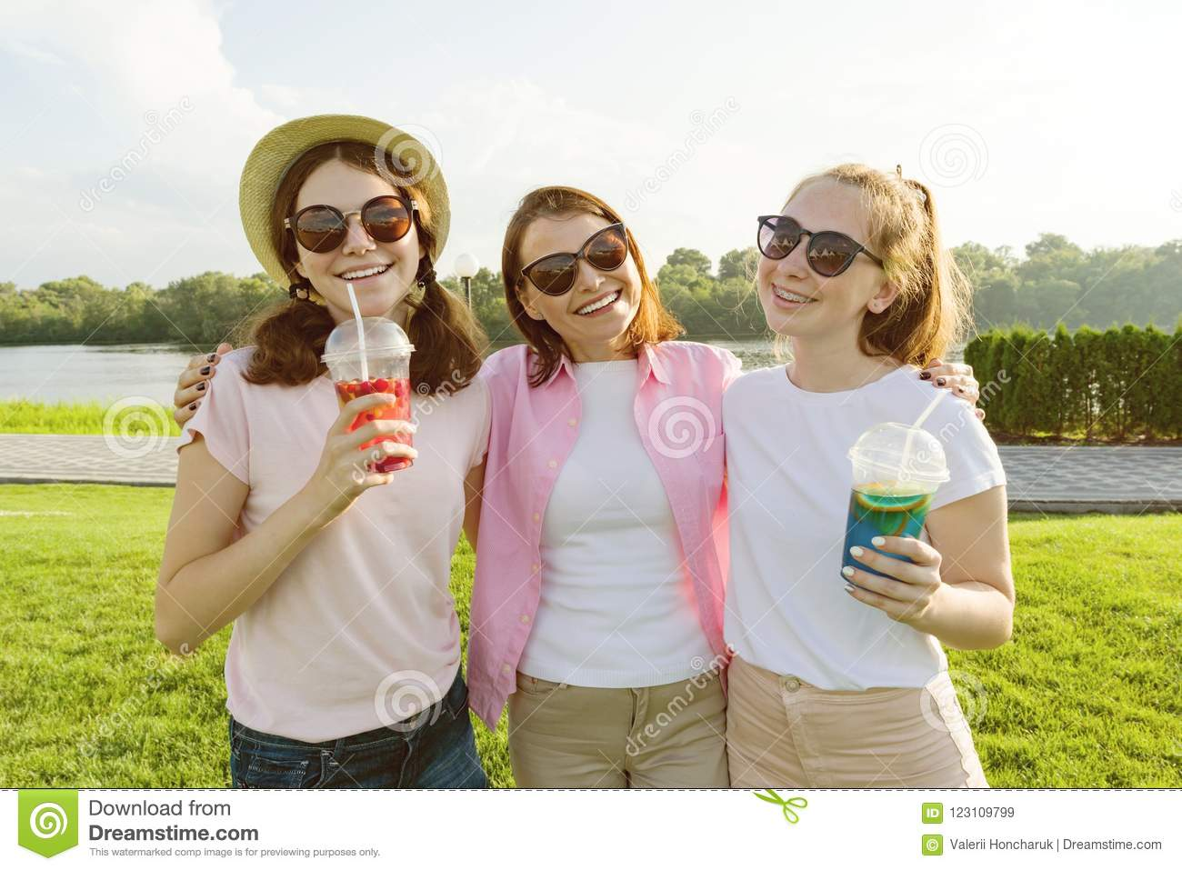 Portrait of happy mother and daughters teenagers 14 and 16 years old, girls with summer drinks. Background nature, recreation area
