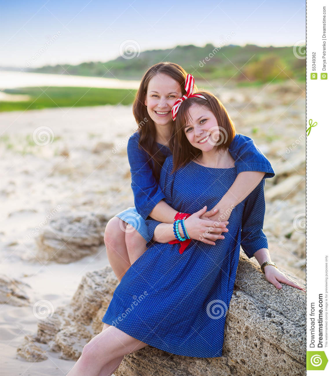 Young Happy Beautiful Family Playing Together On The Beach: Portrait Of A Happy Mother And Her Teen Daughter Stock