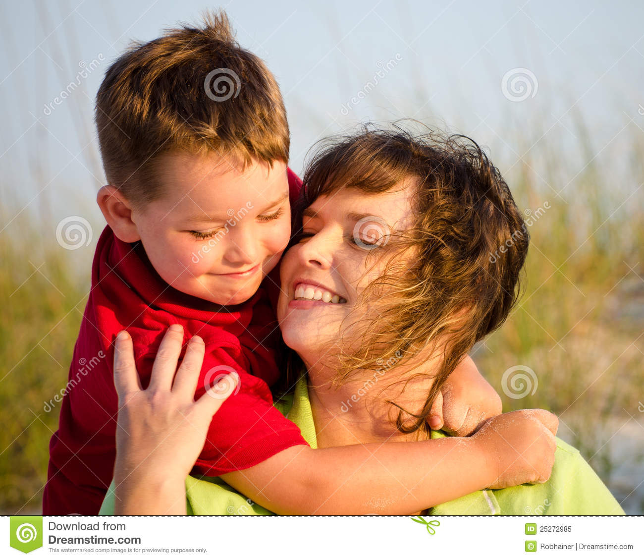 Portrait Of Happy Mother And Son Hugging At Beach Stock