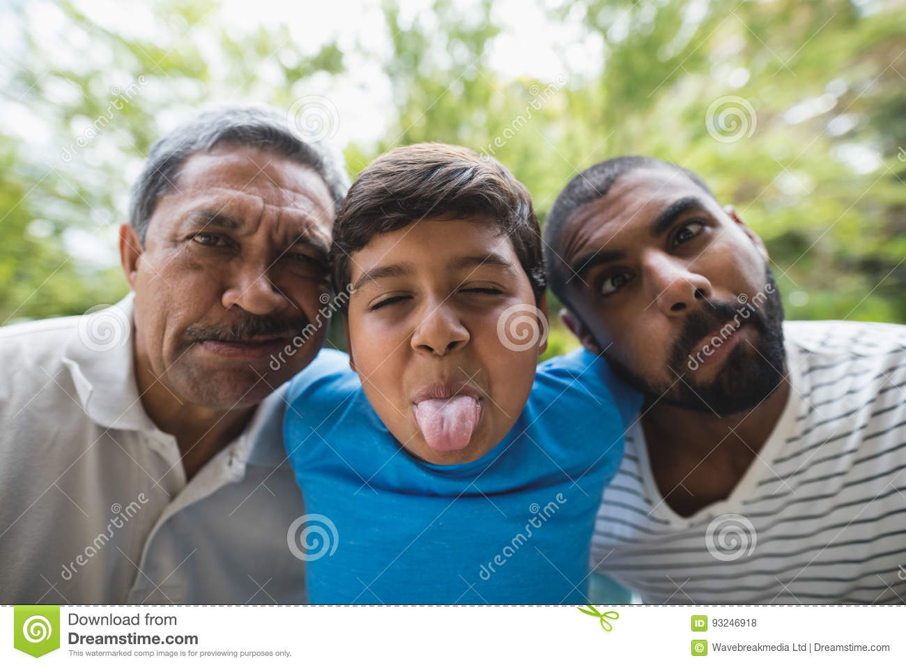 Portrait of happy multi-generation family making faces at park