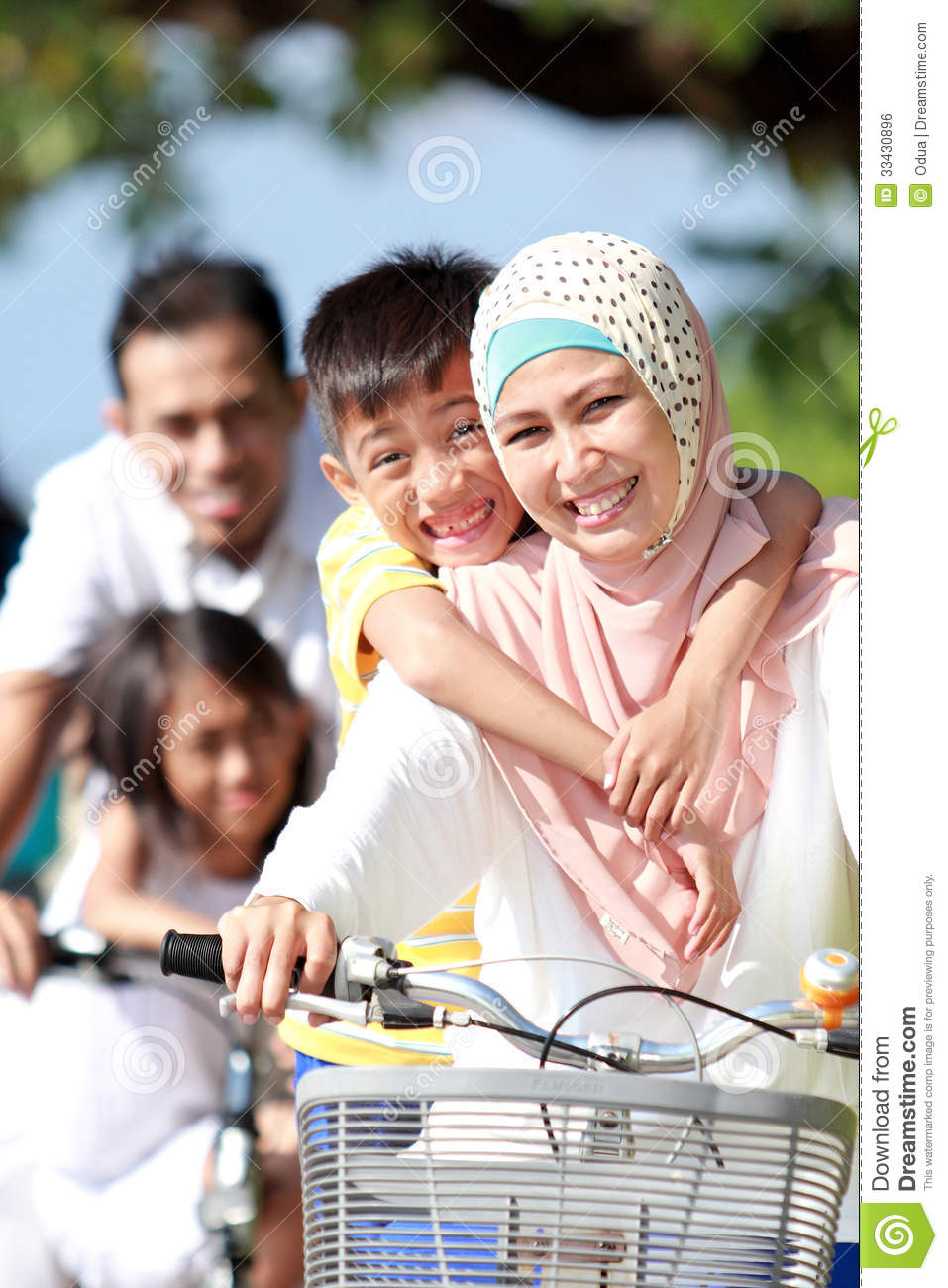 Portrait Of Happy Muslim Family Riding Bikes Together