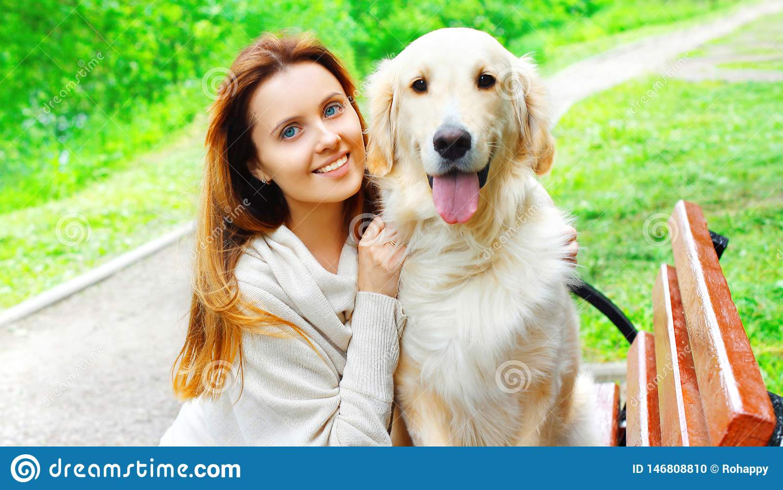 Portrait happy owner woman hugging Golden Retriever dog in city park