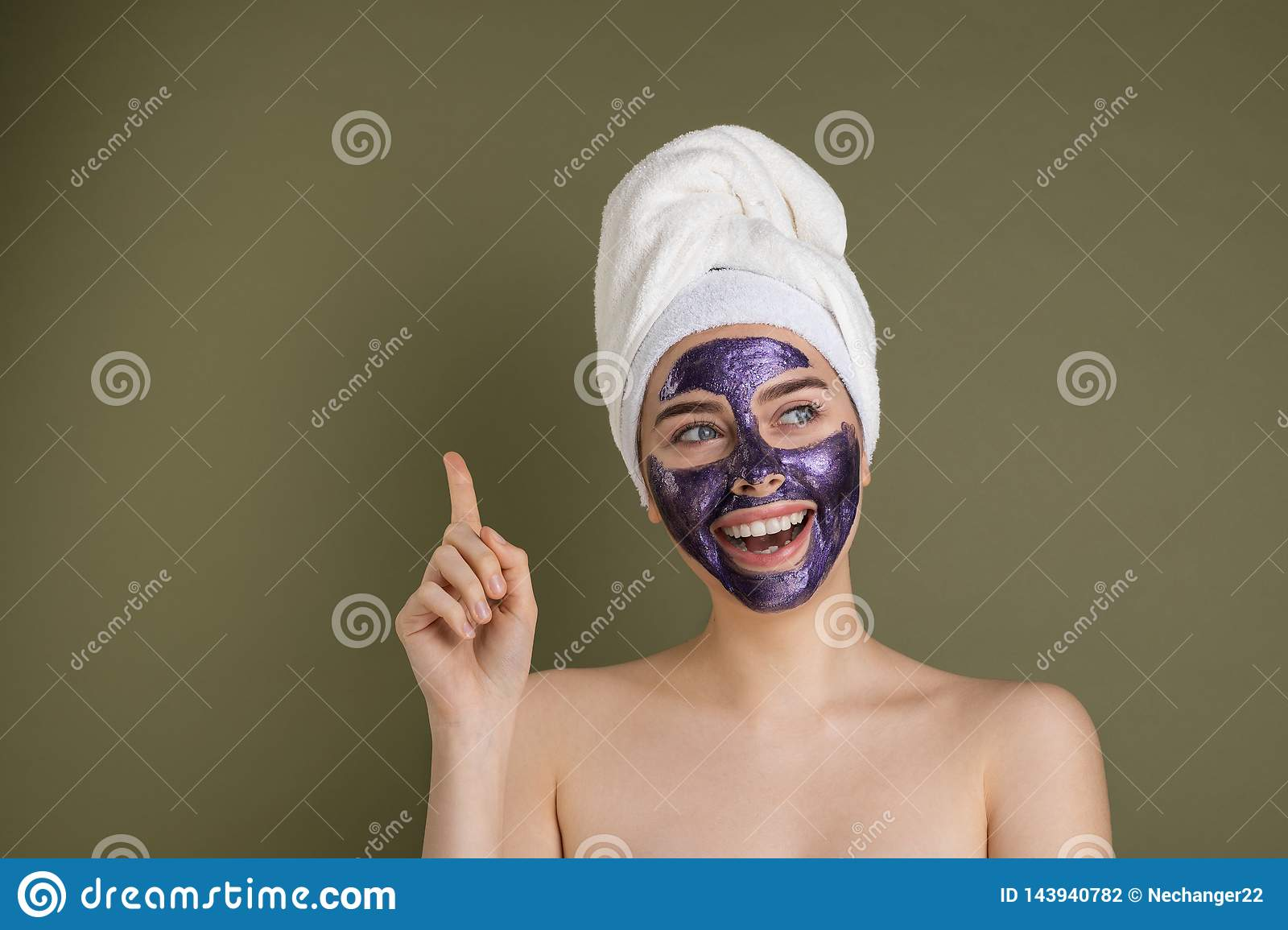 Portrait of a happy and positive naked girl with a purple clay cosmetic mask on her face