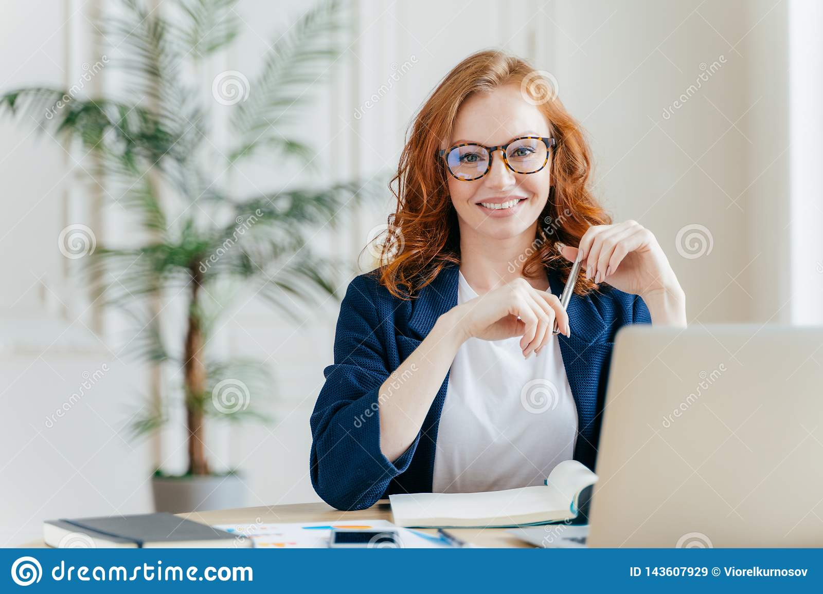 Portrait of happy redhaired woman employee in optical glasses, has satisfied expression, works with modern gadgets, waits for