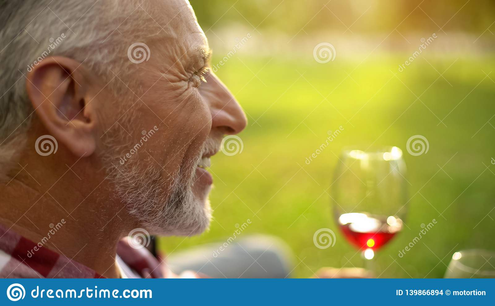 Portrait of happy retired male smiling and drinking wine with wife, anniversary
