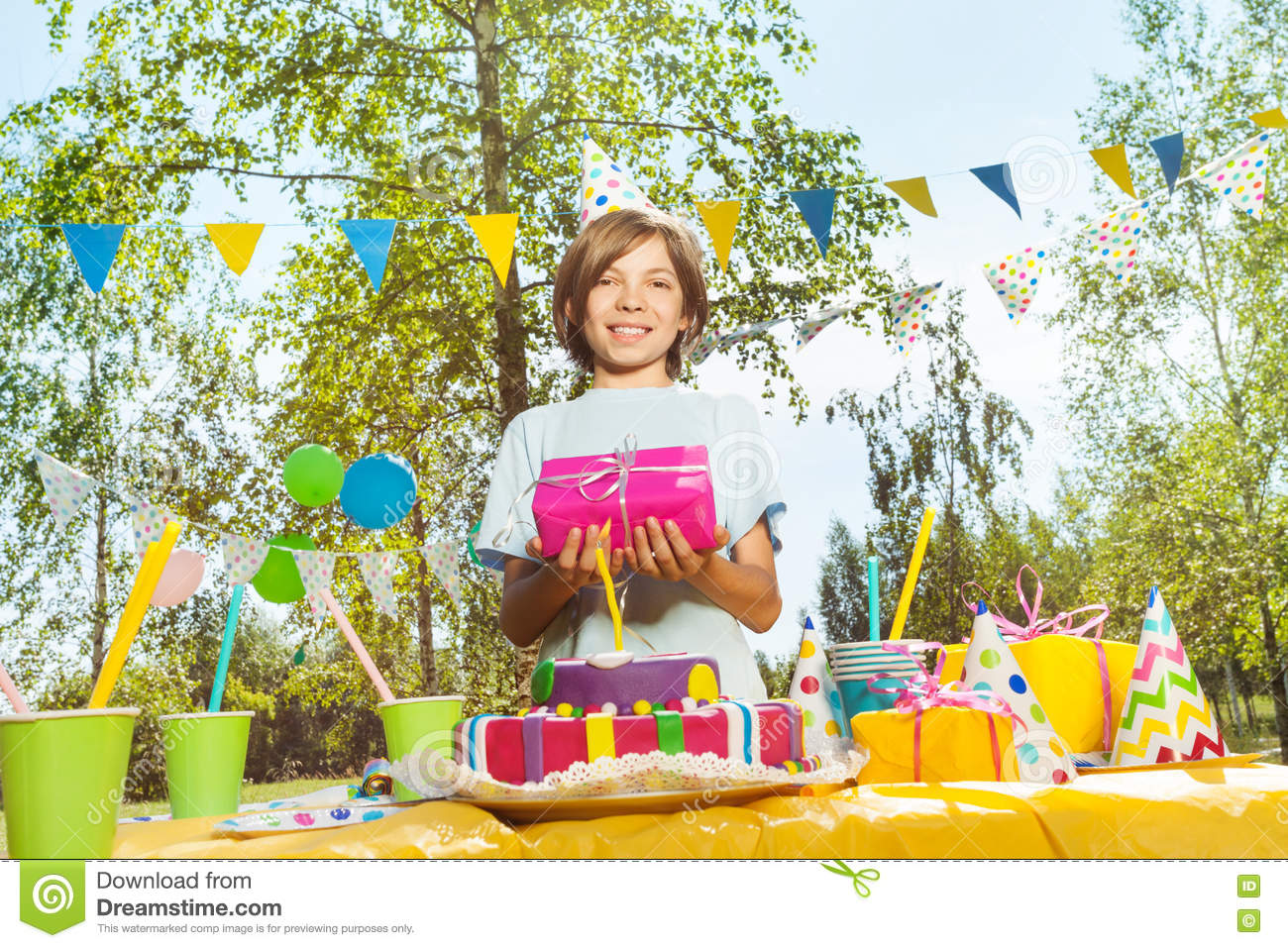 Happy Young Boy In Birthday Hat Holding Box Pink Gift Wrapping Standing Next To The Table With B Day Cake