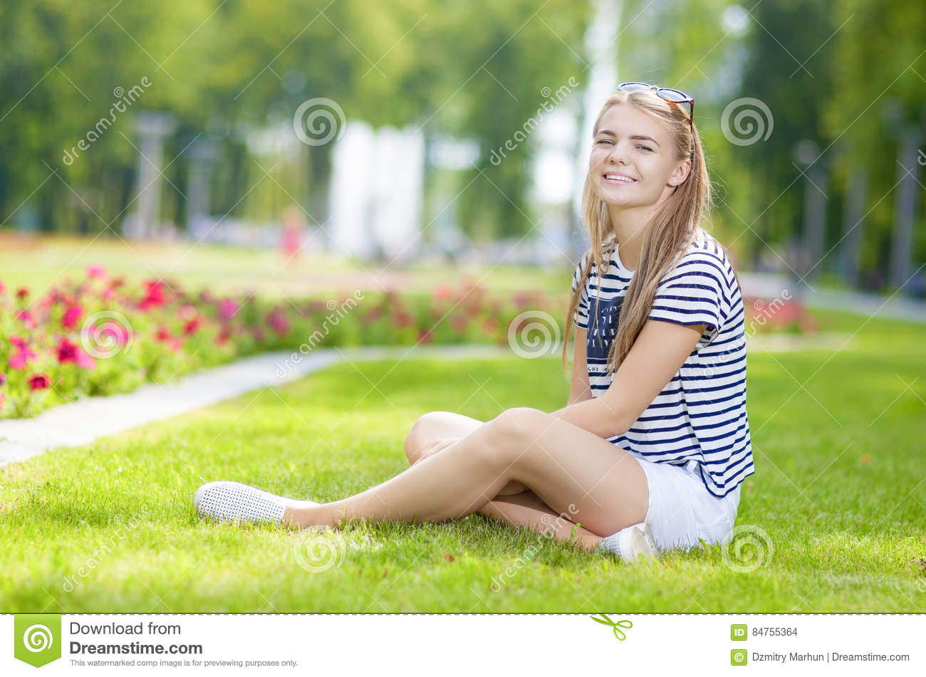 Portrait of Happy Smiling Caucasian Teenage Girl Posing on the Grass in Green Flowery Summer Park