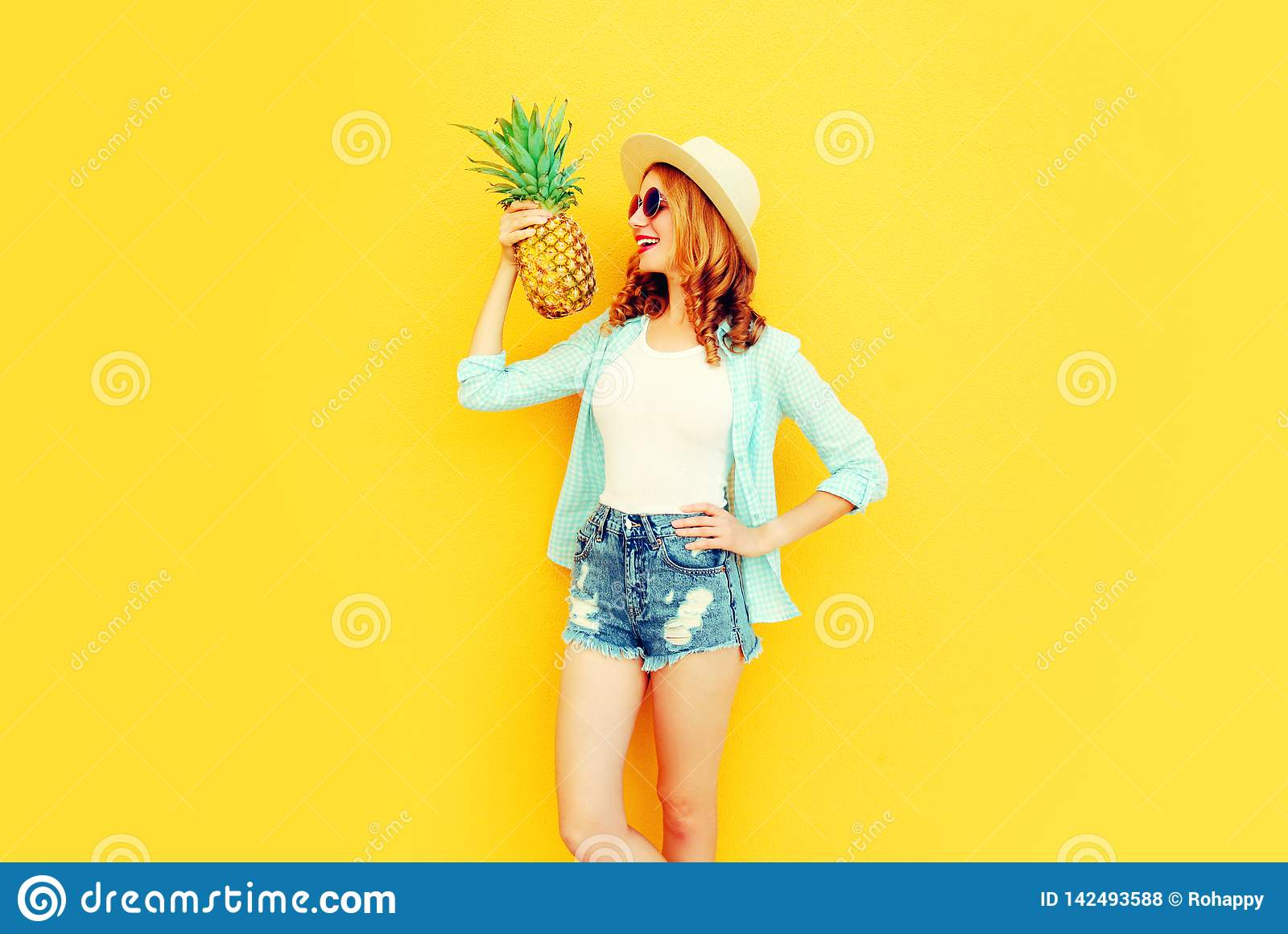 Portrait happy smiling woman holding pineapple having fun in summer straw hat, sunglasses, shorts on colorful yellow