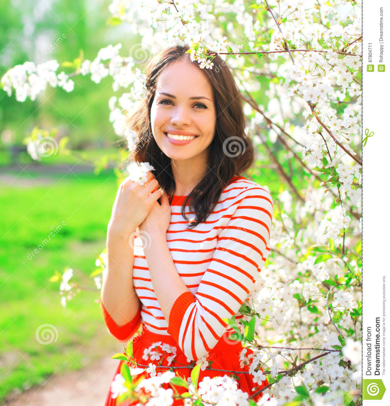 Portrait happy smiling young woman over spring flowers