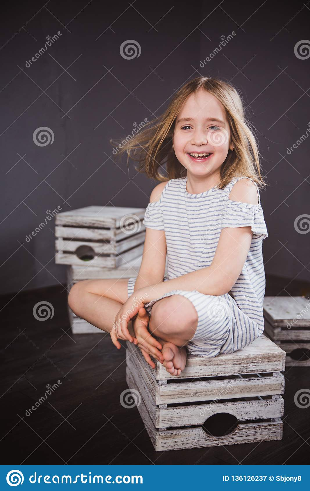 Portrait of a happy teen girl in summer dress in studio. She sits on the boxes, the wind blowing her hair