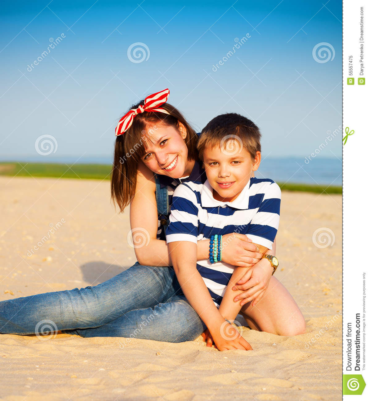 Young Happy Beautiful Family Playing Together On The Beach: Portrait Of Happy Teen Sister And Little Brother Stock