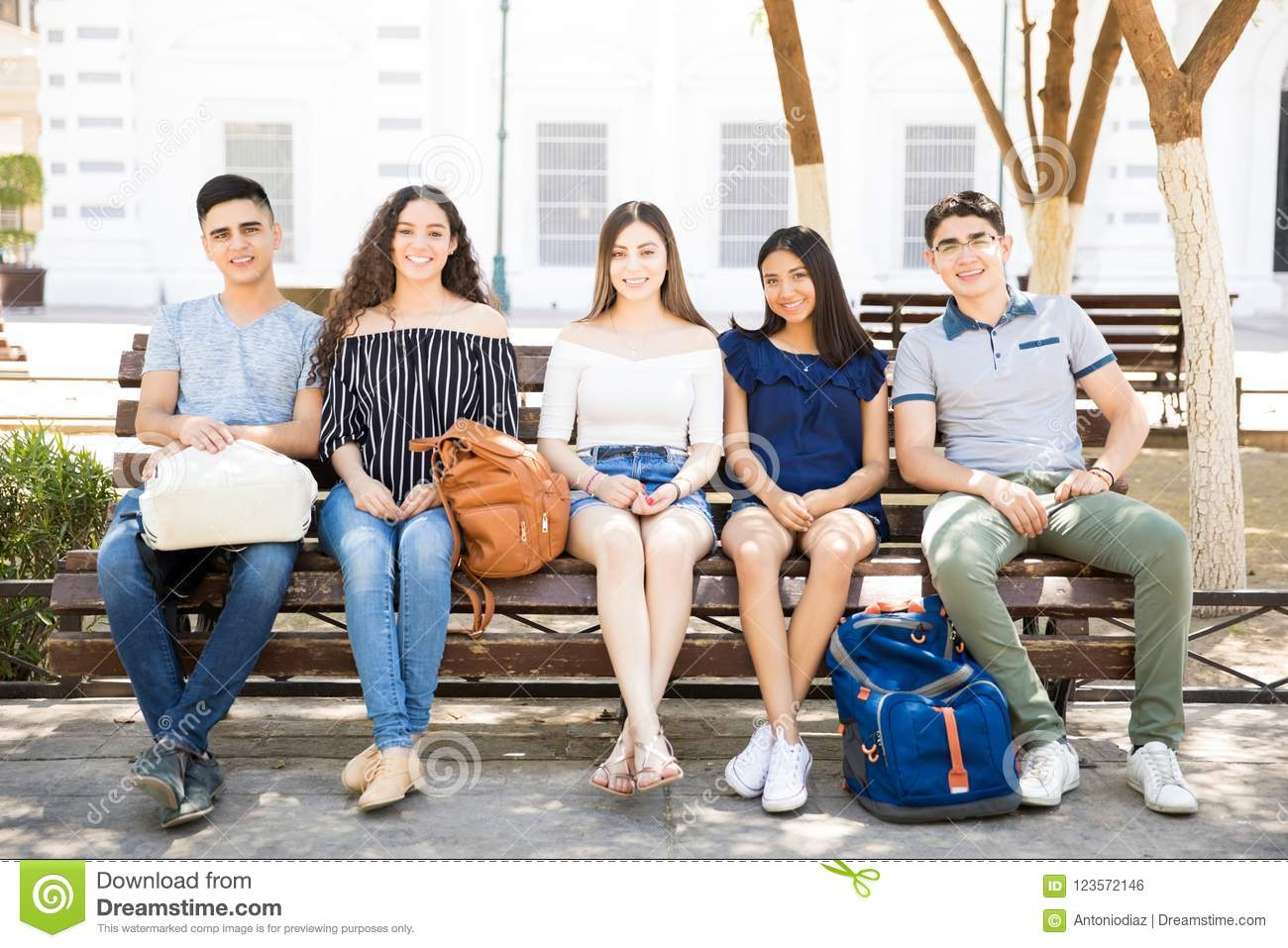 15b19dcfdf1 Portrait of happy teenage boys and girls sitting on a bench outdoor with backpacks  looking at camera and smiling