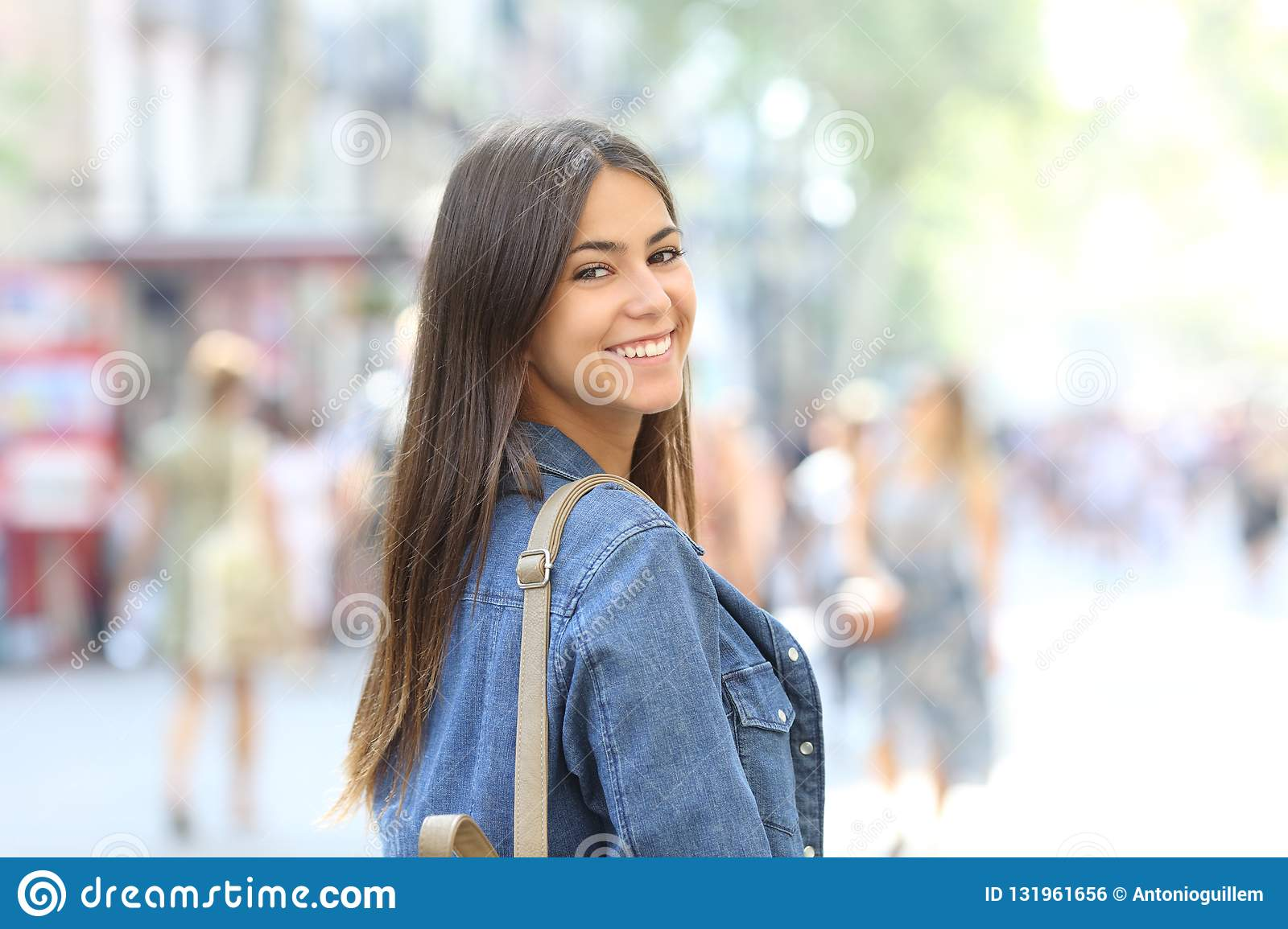 Happy teenage girl looks at camera in the street