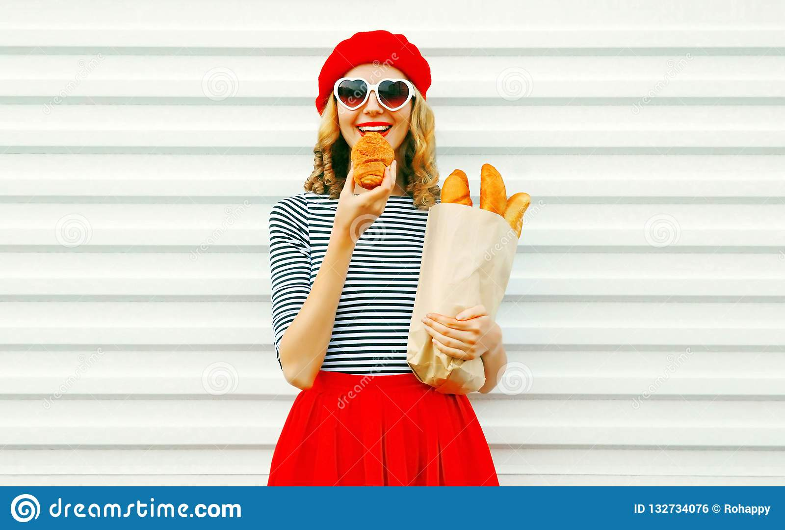 Portrait happy woman eating croissant holding paper bag with lon