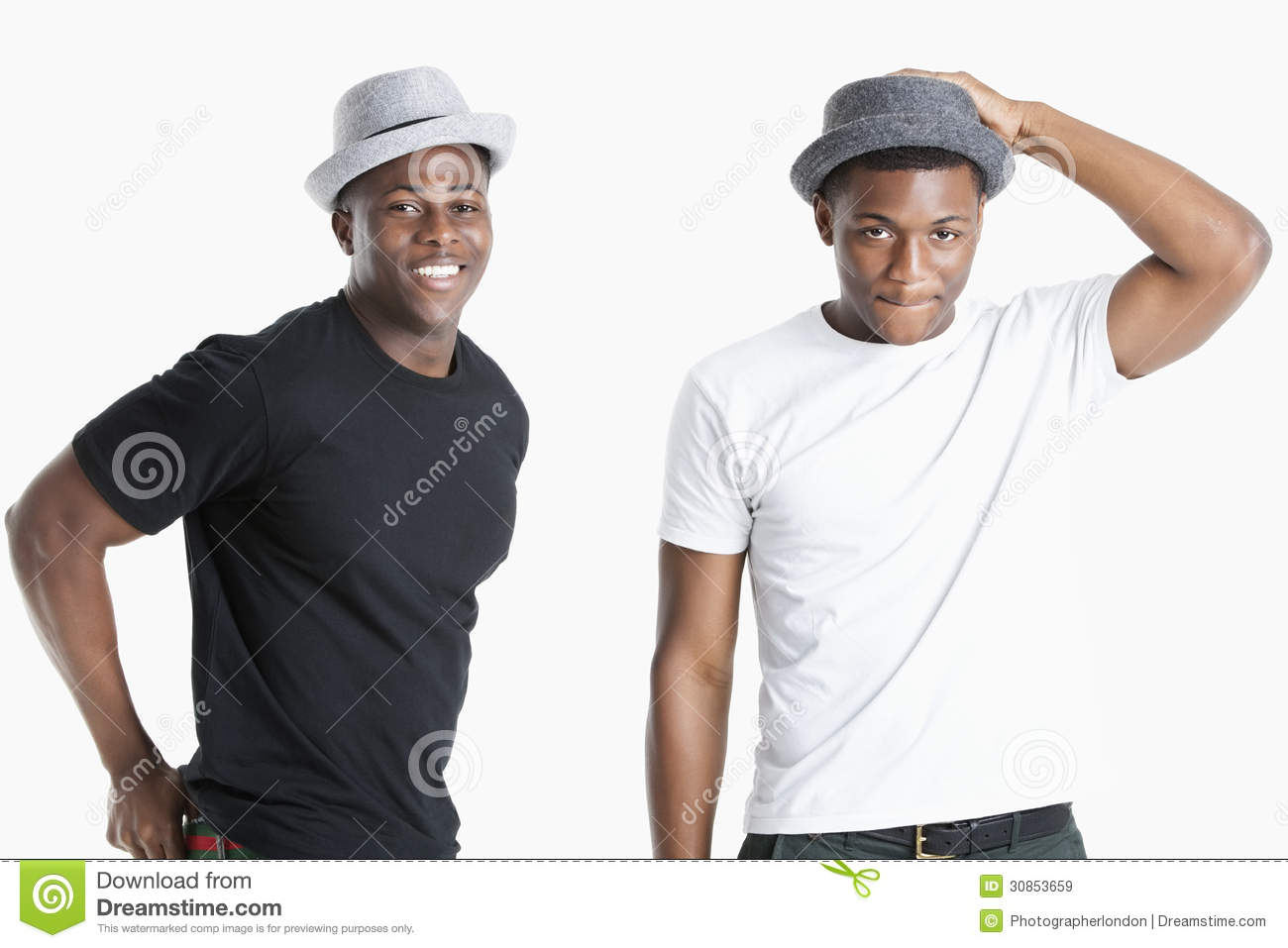 Portrait of happy young African American men wearing hats over gray background