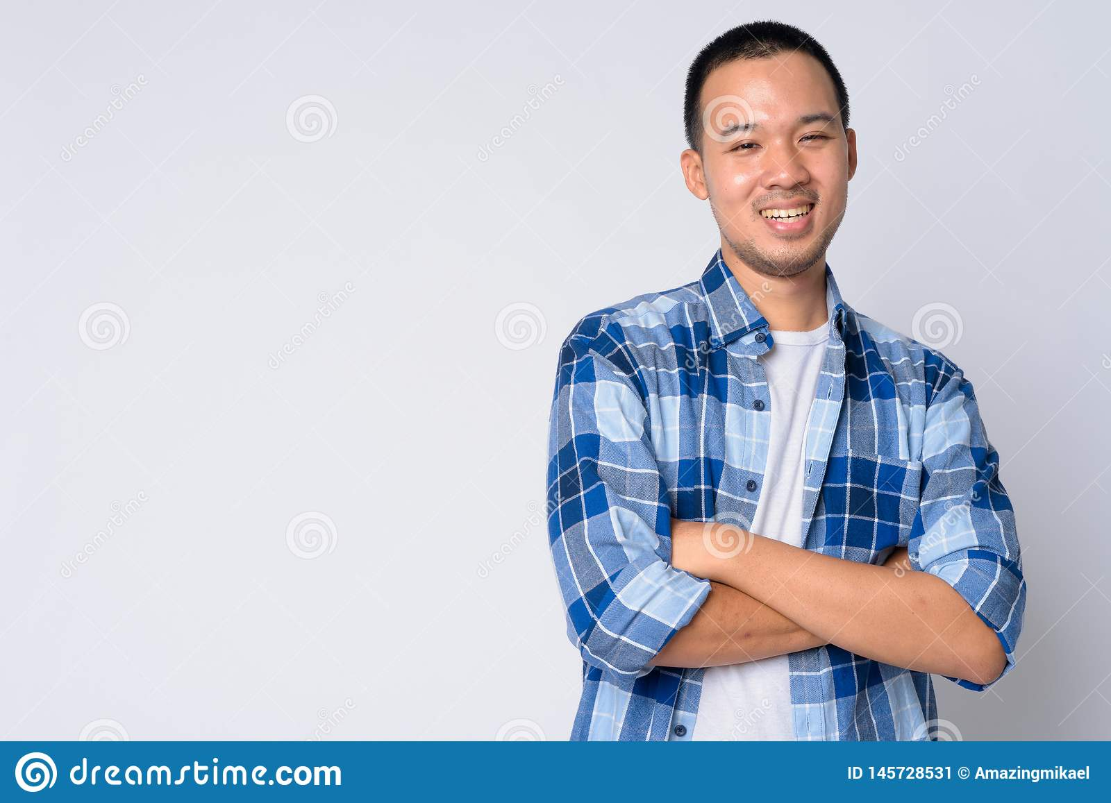 Portrait of happy young Asian hipster man smiling with arms crossed