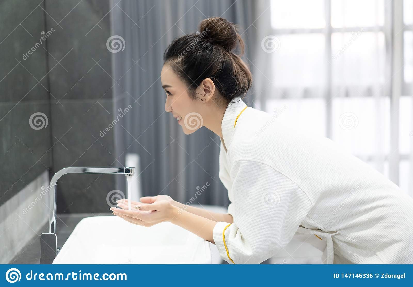 Portrait of happy young Asian woman while washing her face and  looking to mirror at bathroom.Natural skin care and people Concept