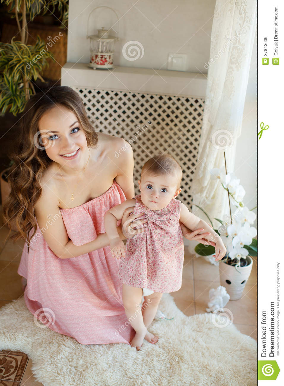 Portrait of happy young attractive mother playing with her baby girl near window in interior at haome. Pink dresses on mother and