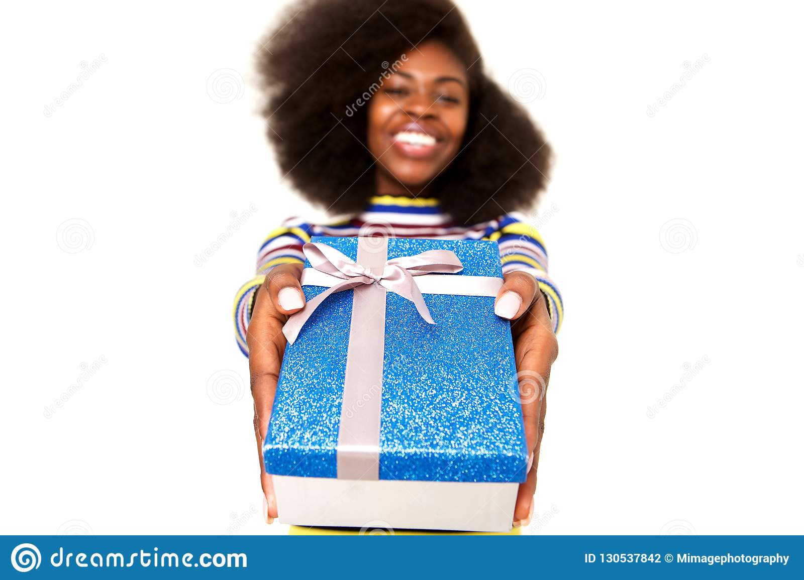 Happy young black woman holding gift box against white background