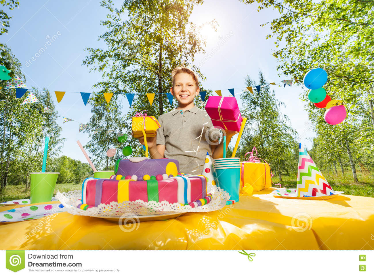 Portrait Of Happy Smiling Boy Holding Birthday Gifts Standing Next To The Cake At Outdoor Party