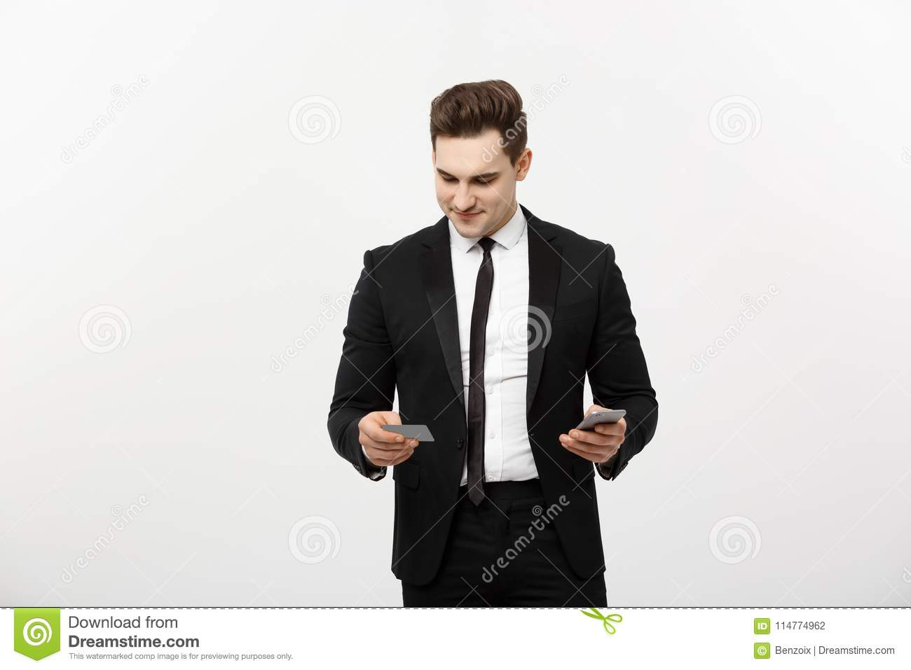 c81724debd00 Portrait of happy young businessman in smart black suit standing over white  wall background. Holding