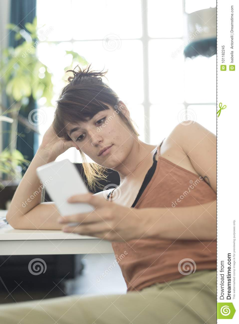 Portrait of happy young businesswoman using mobile phone in offi