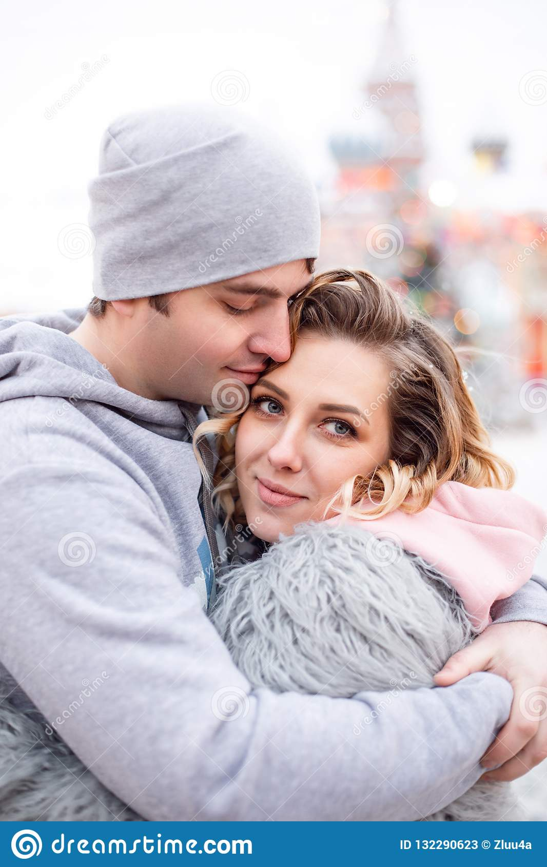 Portrait happy young couple in love at warm winter day, man hugs woman wearing eco fur, tenderness moment