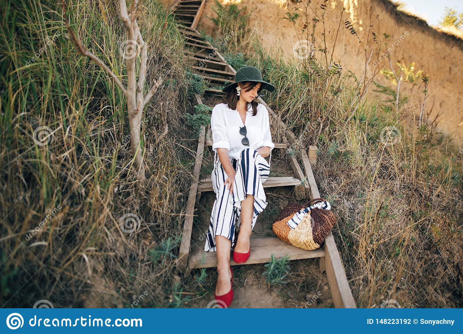 Portrait of happy young fashionable woman relaxing on tropical island. Stylish boho girl in hat sitting on wooden stairs at sandy