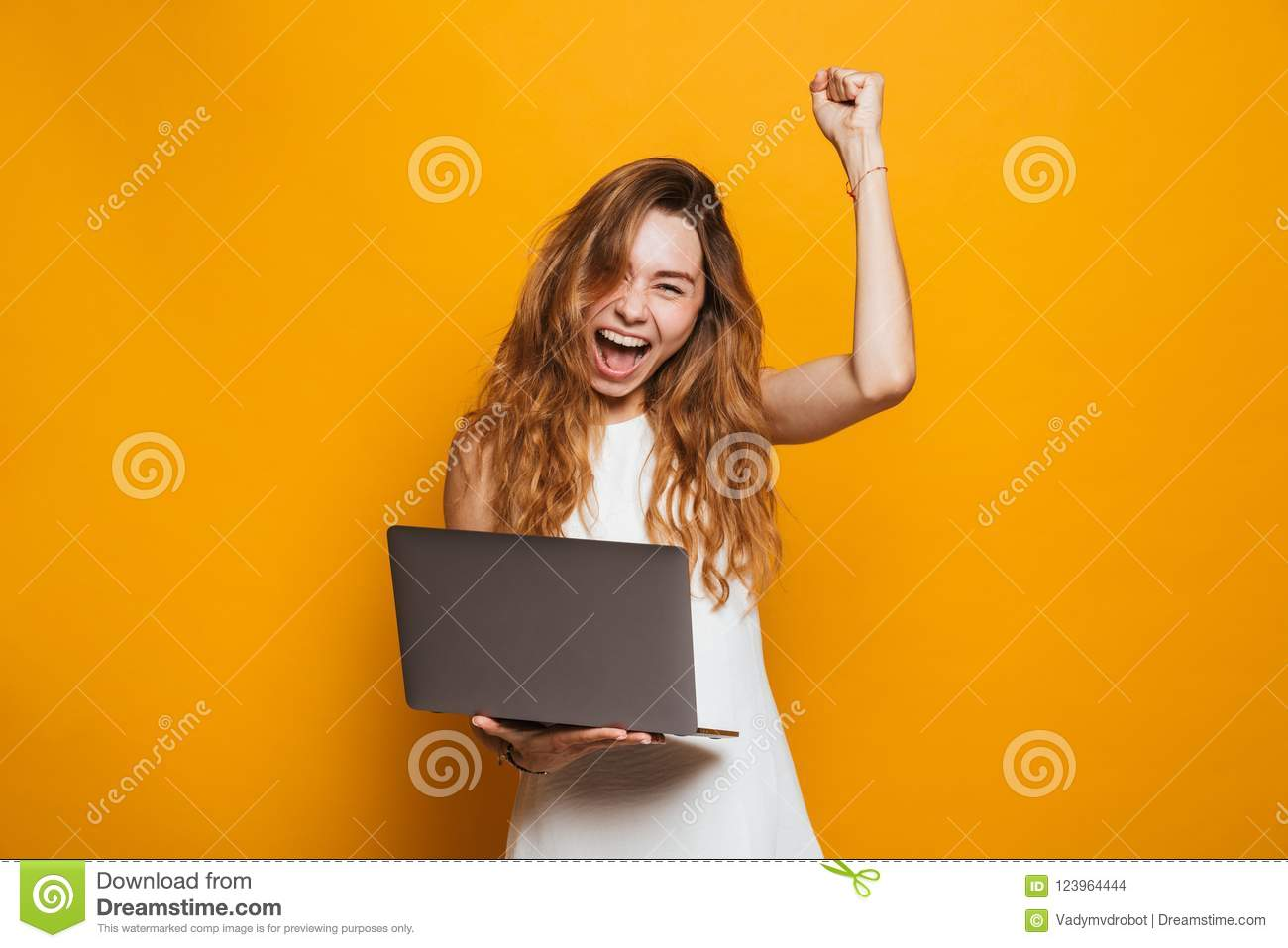 Portrait of a happy young girl holding laptop computer