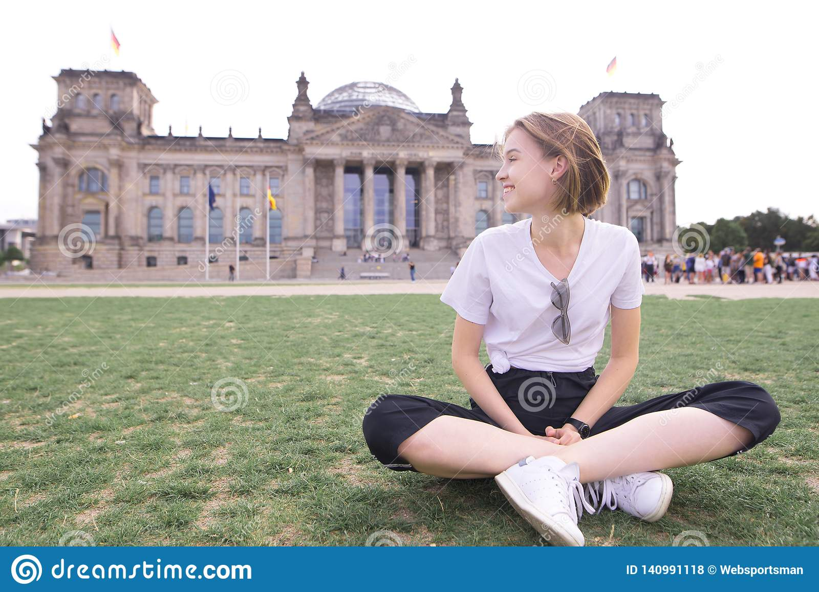 Portrait of a happy young girl sitting on the background of a historic building and smiling.girl traveler in Berlin