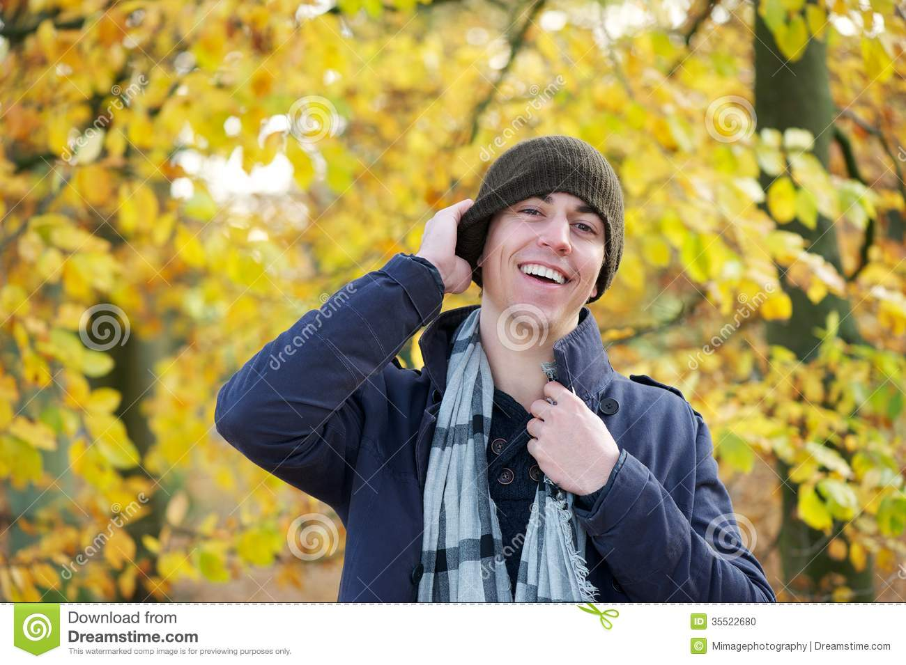 Portrait of a happy young man laughing outdoors with hat